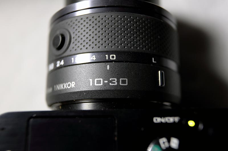 Nikon 1 J3 - Objektiv kann direkt zum Einscahlten der cam benutzt werden. Knopf drücken, Objektiv drehen -> An ... umgekehrt -> aus